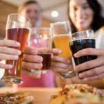 Friends enjoying different beers with food